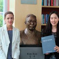 Jung Hwa Kim '08 (right) presenting the book to Sarah Baldwin-Beneich, communications director of the Watson Institute, at the Kim Koo Library.