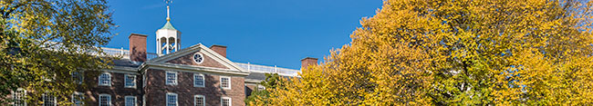 University Hall flanked by bright yellow leaves and crisp blue sky