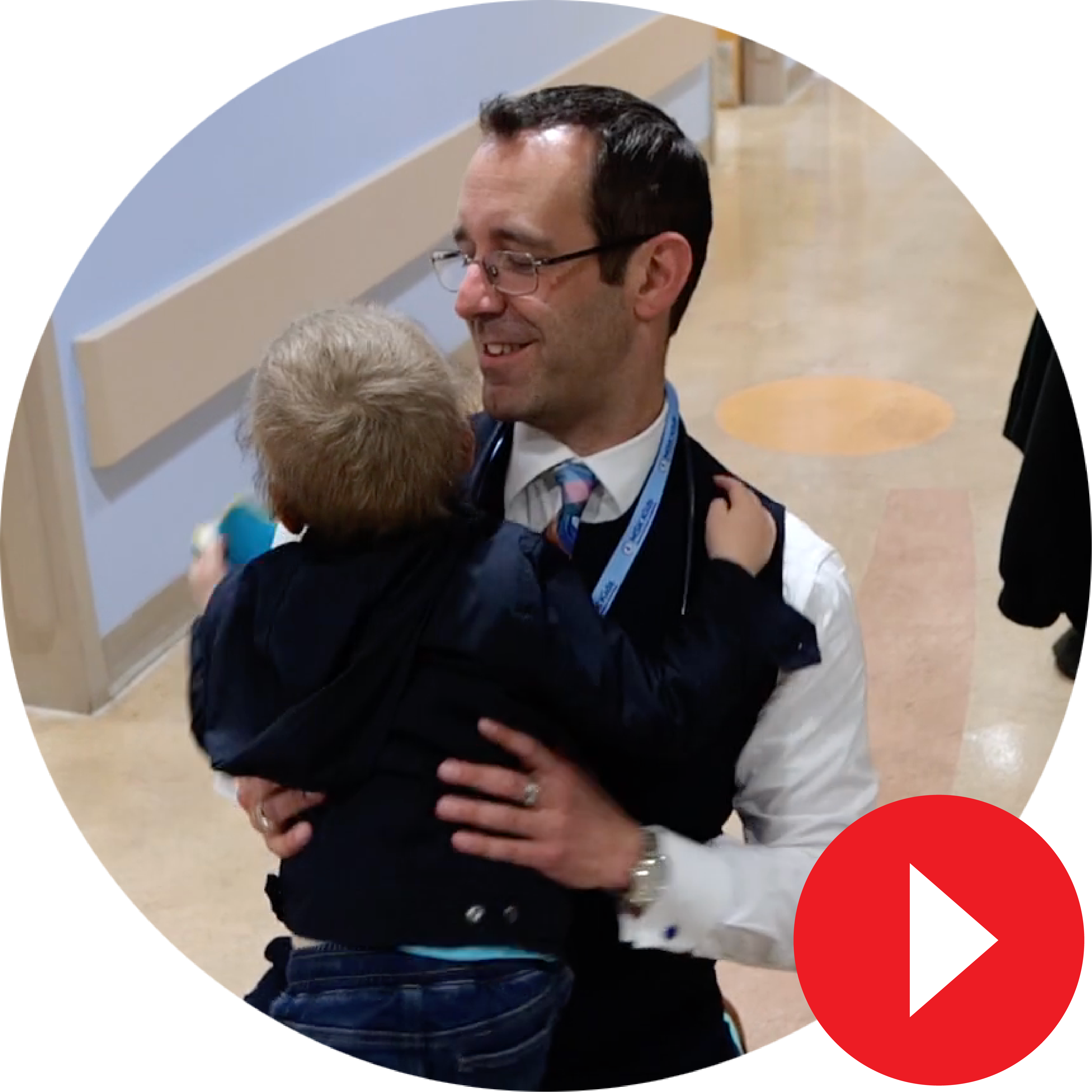 Dr. Gilheeney hugging a patient overlayed by a play video icon